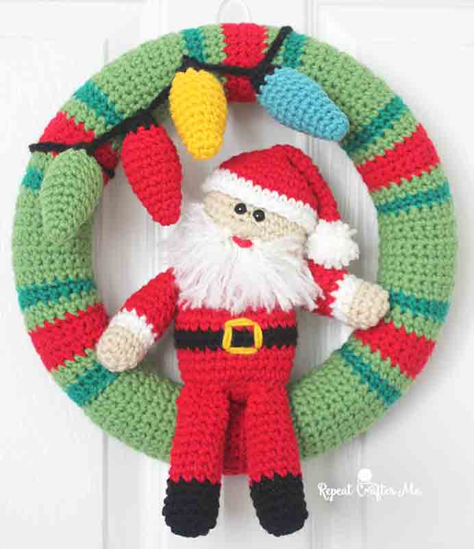 Crocheted Christmas Wreath with Santa front and centre and little Christmas Lights. This crochet pattern by designer Sarah at Repeat Crafter Me is simply gorgeous. Please share. Join now for creative craft inspiration. The best in craft delivered to your inbox every Monday - CraftyLikeGranny.com #crochet