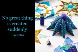 Pin Cushion that looks like a starfish on a table with quilted star pieces and blue cotton thread.