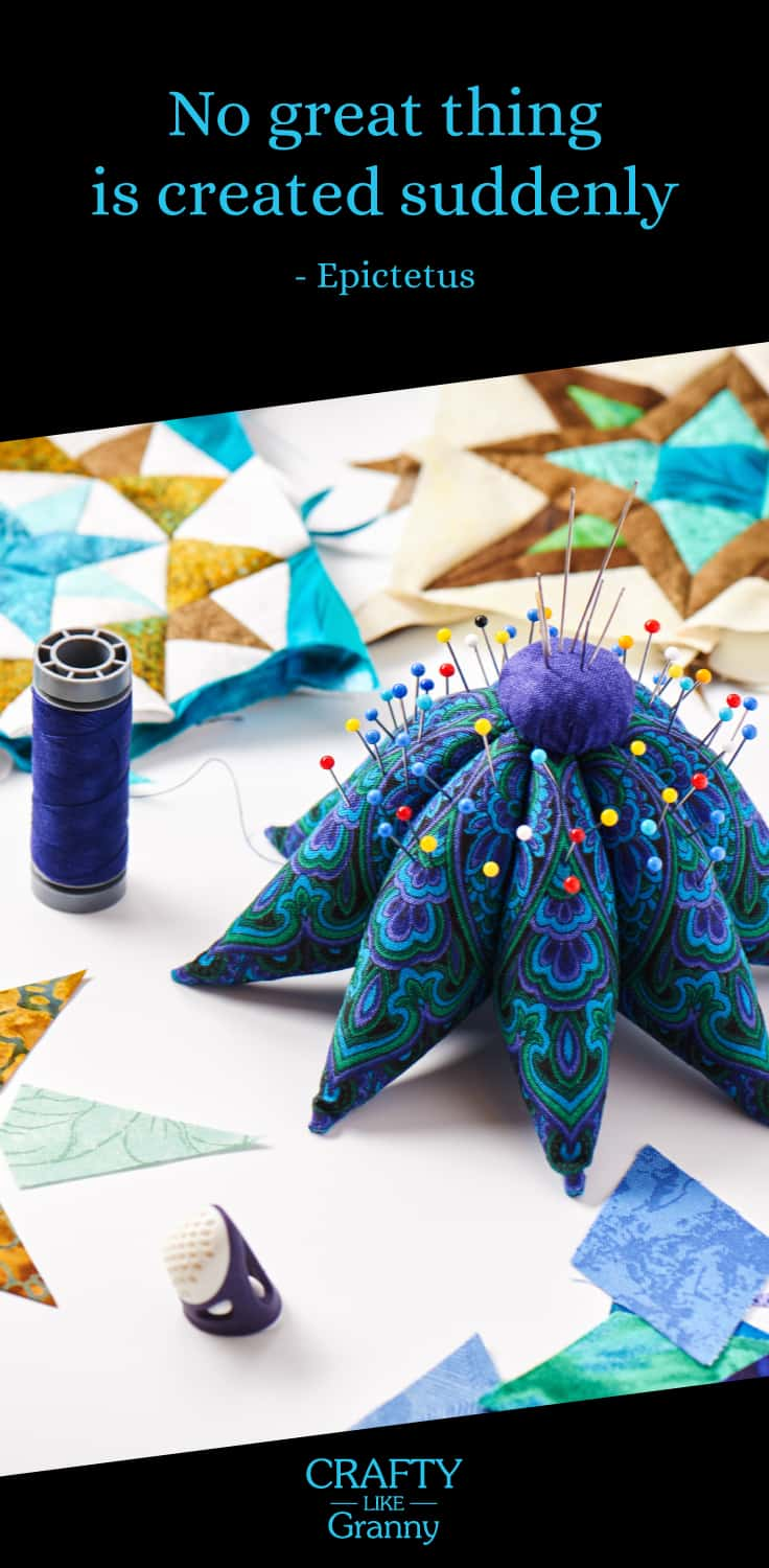 Quilting pieces in a star pattern in blues and golds. Pin Cushion that looks like a starfish and reel of dark blue thread.
