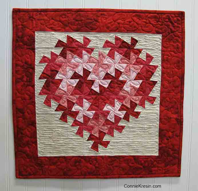 Twisting Heart Valentine Quilt Tutorial. In keeping with the spirit of Valentine's Day, this gorgeous quilt is a small enough project to get done before 14 Feb!! Follow Connie from Freemotion by the River's step by step instructions.Please share. You will always look forward to Mondays, with our craft inspiration roundups -CraftyLikeGranny.com #quilting