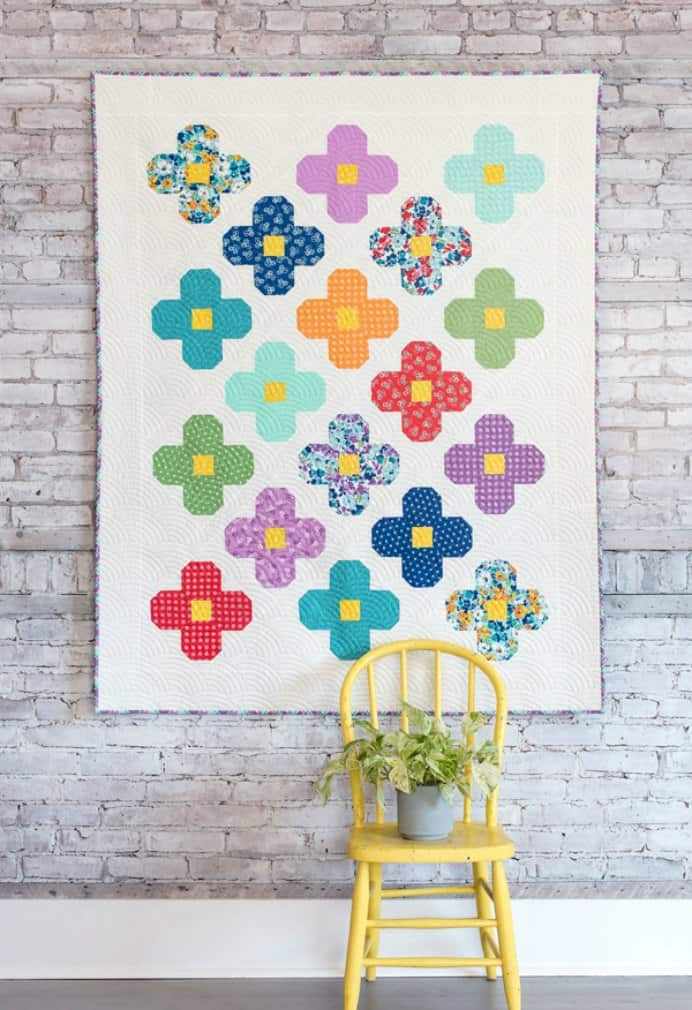 Flowers in bloom inspired quilt by Allison at Cluck Cluck Sew. A beginner friendly pattern if you have a few quilts under your belt and have some piecing experience. Please share. You will always look forward to Mondays, with our craft inspiration roundups -CraftyLikeGranny.com #quilting #quilt #quiltblock #sewing