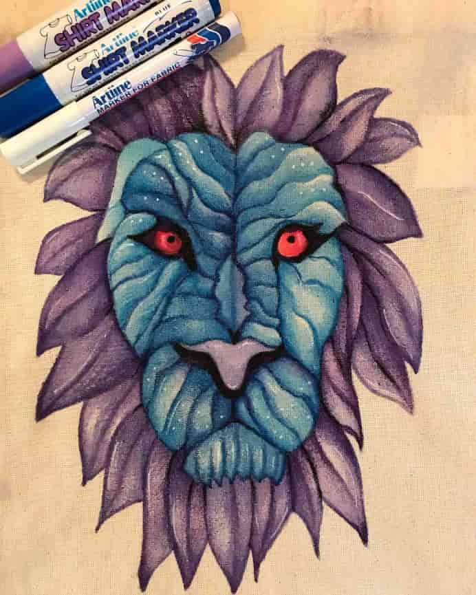 art_byjudith on Instagram Lion Face in aqua and purple on Fabric created with Artline Fabric markers in aqua and purple